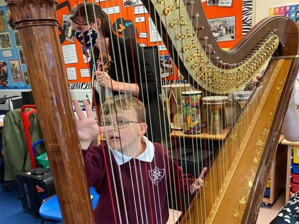 visually impaired student of Priestly Smith playing harp with the Swans